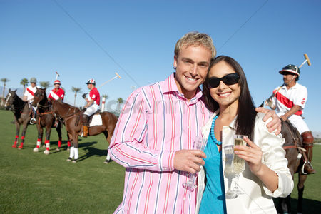 Celebrating : Couple standing arms around celebrating with champagne at a polo match