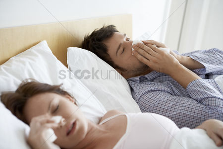 Blowing : Couple with colds lying in bed