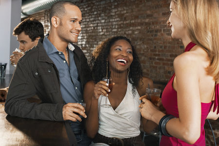 Friend : Couple with friend holding drinks laughing standing at bar