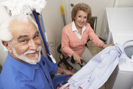 Retirement : Couple with laundry by washing machine