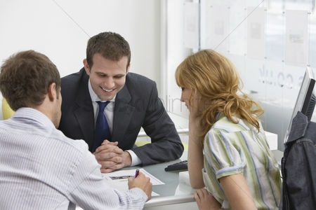 Business suit : Couple with real estate agent in office man writing