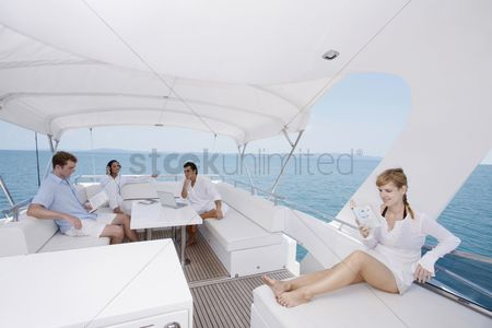 Three quarter length : Couples relaxing on yacht