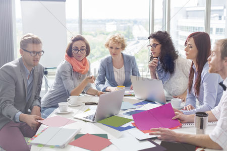 Businesswomen : Creative business colleagues analyzing photographs at conference table in office