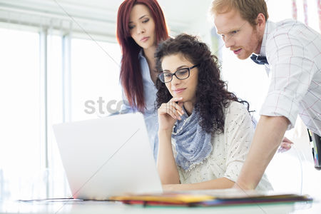 Three quarter length : Creative business colleagues using laptop at desk in office