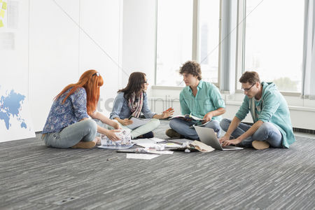 Creativity : Creative businesspeople discussing while sitting on floor in office