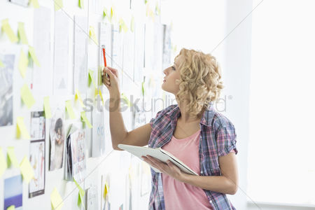 Businesswomen : Creative businesswoman analyzing papers stuck on wall in office