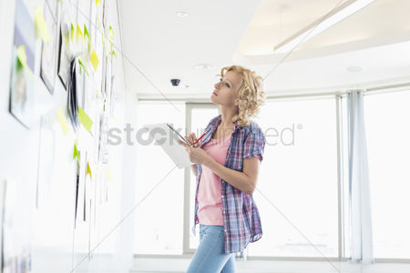 Window : Creative businesswoman looking at papers stuck on wall while writing notes in office