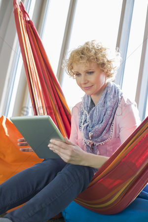 40 44 years : Creative businesswoman using digital tablet on hammock in office