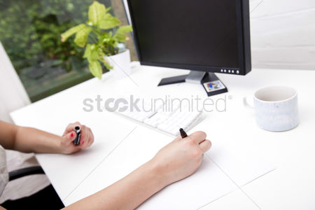 Business : Cropped image of businesswoman noting on paper at computer desk