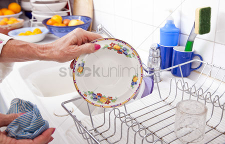 Senior women : Cropped image of senior woman arranging plate in rack at kitchen counter