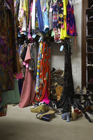 Pile : Crowded clothing racks and piled shoes in second hand store