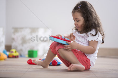 Czech republic : Cute girl playing with toy guitar at home