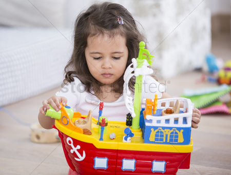Toy : Cute girl playing with toy ship at home