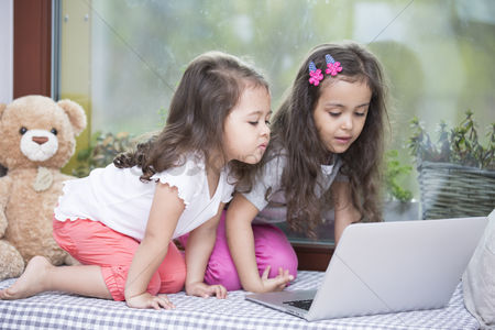 Toy : Cute little sisters using laptop on bed at home