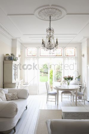 England : Daybed with cushions and glass chandelier in white home interior