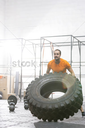 Strong : Dedicated man flipping tire in crossfit gym