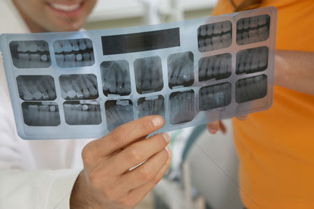Examination : Dentist and patient examining x-rays  close-up