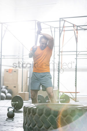 Muscle training : Determined man hitting tire with sledgehammer in crossfit gym