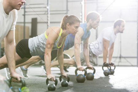 People : Determined people doing pushups with kettlebells at crossfit gym