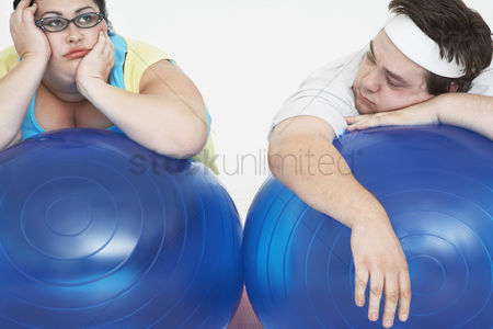 Loss : Disinterested overweight man and woman lying on exercise balls close up