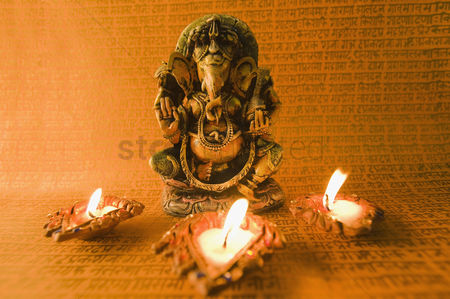 God : Diwali oil lamps in front of an idol of lord ganesha