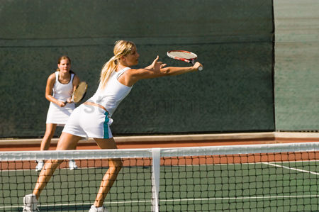 Match : Doubles tennis player stretching to hit tennis ball with backhand