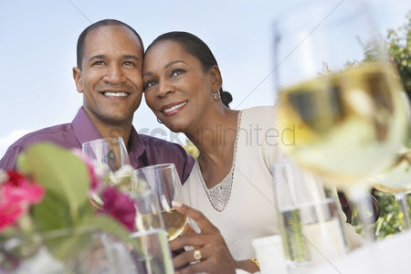 40 44 years : Elegant couple cheek to cheek holding wine glasses at garden party table