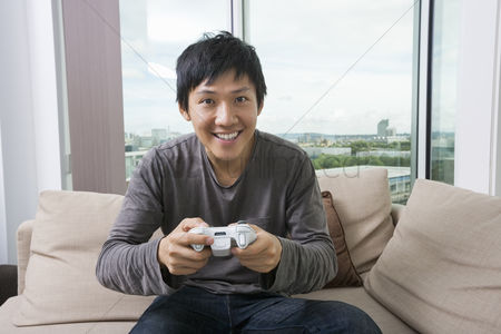 Excited : Excited mid adult man playing video game on sofa