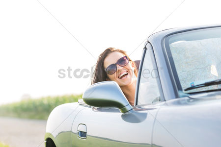Transportation : Excited woman enjoying road trip in convertible against clear sky