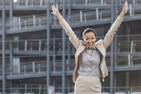 Three quarter length : Excited young businesswoman with arms raised standing against office building