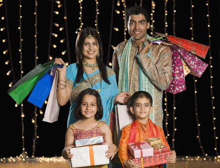 Diwali : Family carrying shopping bags and gifts for diwali