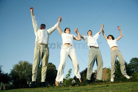 Young boy : Family holding hands while jumping together