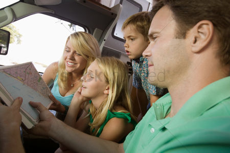 Pre teen : Family in rv looking at road map