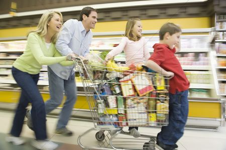 Shopping cart : Family of four run with full shopping trolley