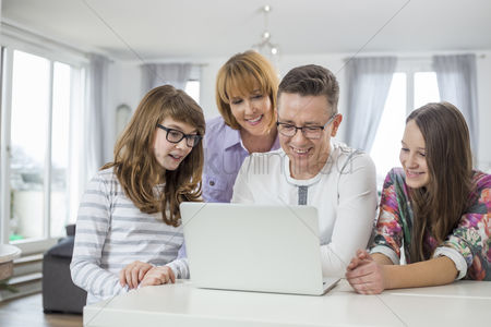 Internet : Family of four using laptop together at table in home