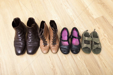 Variety : Family shoes placed in a row on hardwood floor