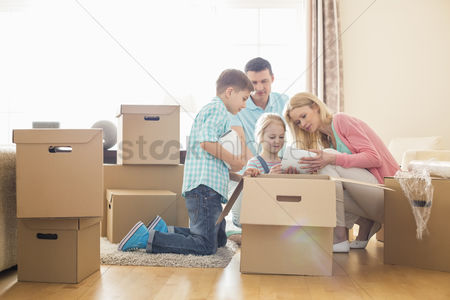 Two people : Family unpacking cardboard boxes at new home