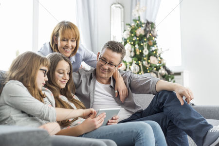 Internet : Family using tablet pc on sofa with christmas tree in background