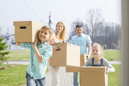Pre teen : Family with cardboard boxes moving into new house