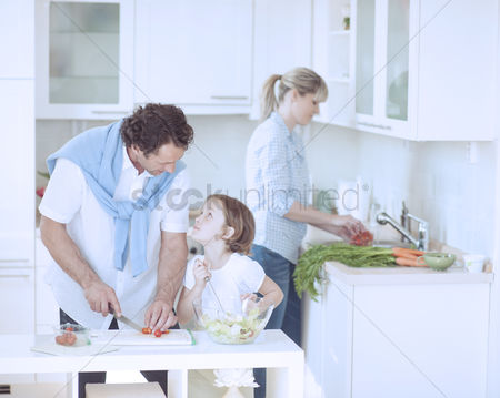 Offspring : Father and daughter looking at each other whilst preparing healthy meal in kitchen