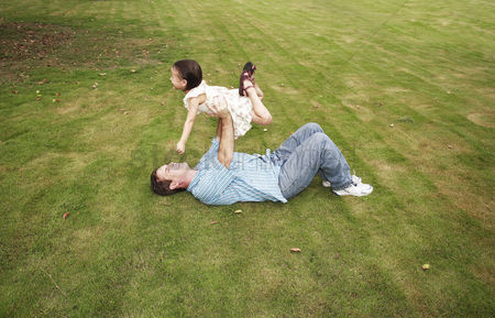 Daughter : Father and daughter playing on the grass