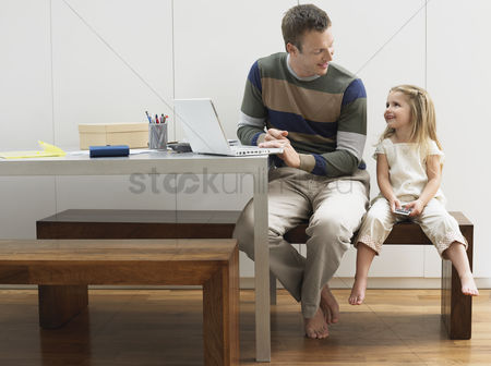 Furniture : Father and daughter using laptop and cell phone