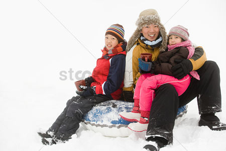 Sitting on lap : Father and kids having warm drink in snow