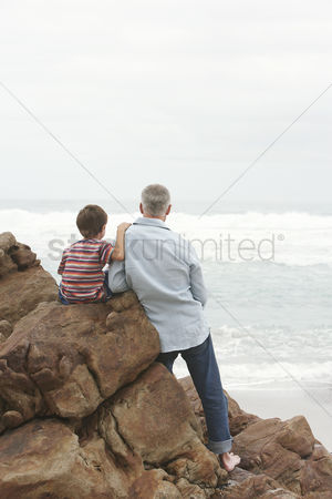 Denim : Father and son  5-6  sitting on rock facing ocean back view
