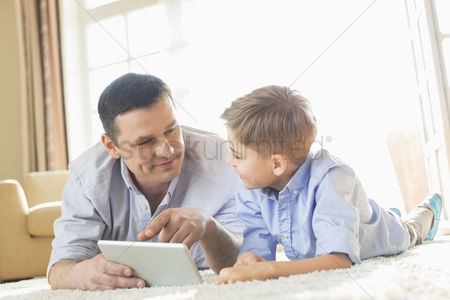 40 44 years : Father and son using digital table on floor at home