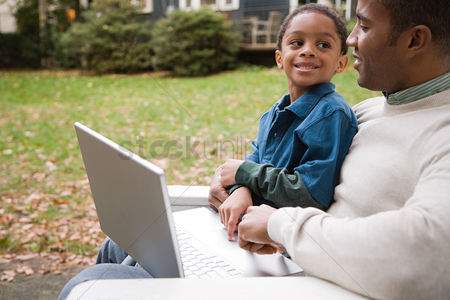 Sitting on lap : Father and son with laptop