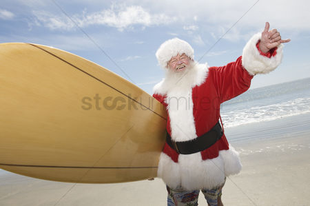 Jacket : Father christmas stands with a surfboard at the beach
