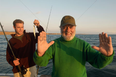 Posing : Father gesturing fish size on boat  portrait