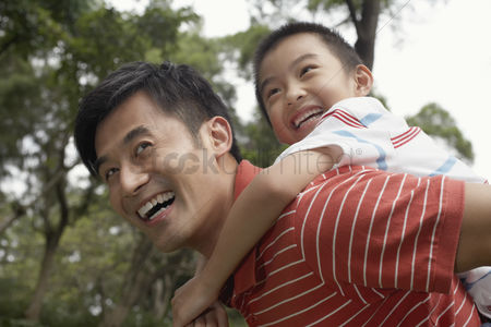 Trees : Father giving son piggyback  7-9  in park