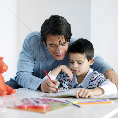 Learning : Father watching son doing homework